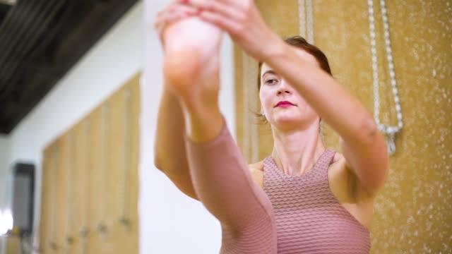 young woman stretching in yoga studio in slow motion - posizione corretta video stock e b–roll