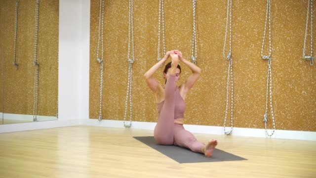 young woman stretching in yoga studio with free space, copy space - posizione corretta video stock e b–roll