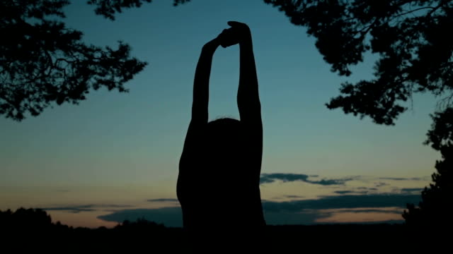 Young woman stretching towards the sky in the forest after sunset video
