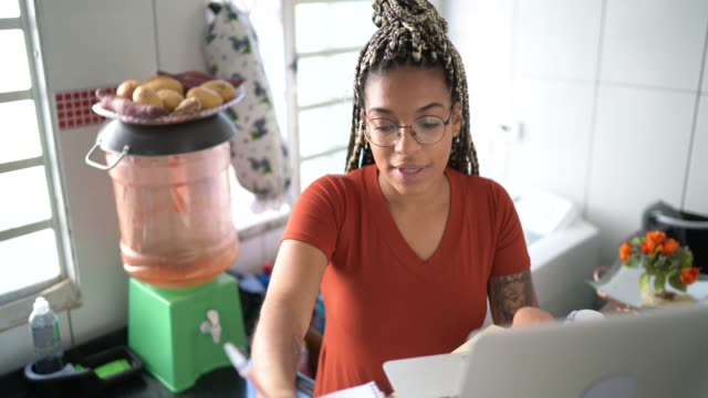 Young woman studying with laptop on a online class at home Young woman studying with laptop on a online class at home financial planning stock videos & royalty-free footage