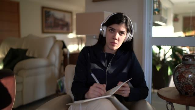 vidéos et rushes de jeune femme étudiant avec la leçon en ligne de vidéo à la maison - workshop