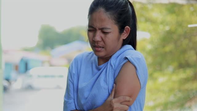 giovane donna che soffre di sensazione dolorosa nei muscoli del braccio, concetto di assistenza sanitaria - fragilità video stock e b–roll