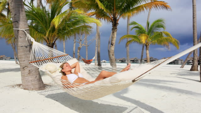 Young woman sunbathing in a hammock. video