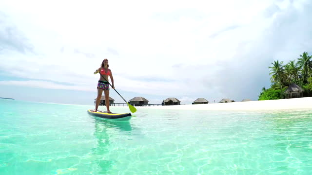 Young woman SUP boarding in sunny exotic island resort video