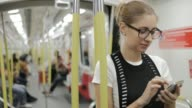 istock Young woman surfing in internet by smart phone in subway. 1165868464