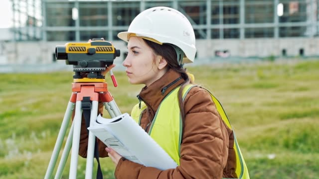 A young woman surveyor in work clothes and helmet adjusts the equipment and produces calculations on the construction site. The concept of landscape design, geodesy A young woman surveyor in work clothes and helmet adjusts the equipment and produces calculations on the construction site. The concept of landscape design, geodesy. quality control stock videos & royalty-free footage