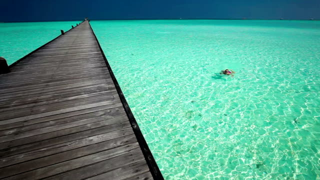 Young woman swimming in a coral lagoon next to jetty video