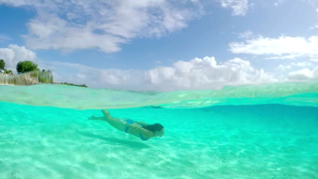 SLOW MOTION UNDERWATER: Young woman swimming in crystal clear ocean video
