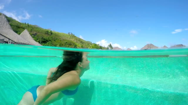 UNDERWATER: Young woman swimming in pool at luxury hotel resort video