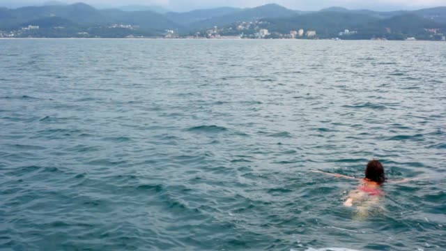 Young woman swimming in sea from camera video
