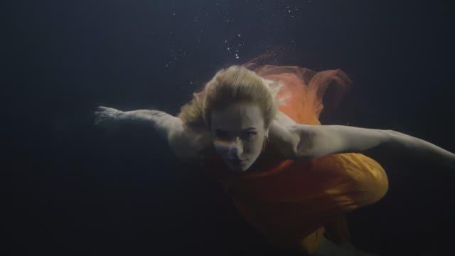 Young woman swimming like fairy mermaid underwater pool on dark background