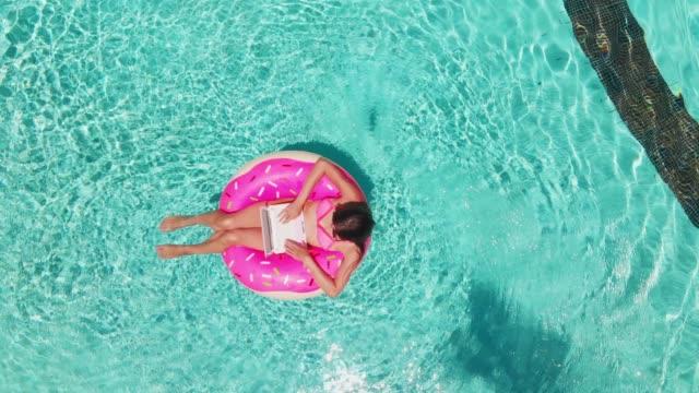 ung kvinna simmar i havet i en simning cirkel. flicka som vilar i poolen på en uppblåsbar cirkel med en dator, uppifrån - inflatable ring bildbanksvideor och videomaterial från bakom kulisserna
