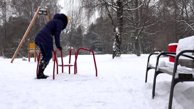 young woman swing in children playground at winter time. FullHD video
