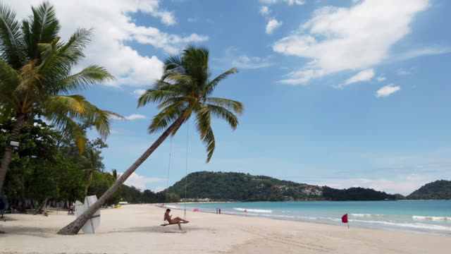 vídeos de stock e filmes b-roll de 4k young woman swing on a beach few people at the patong beach due to covid-19 - phuket