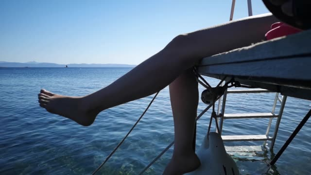 Young woman swinging legs on pier