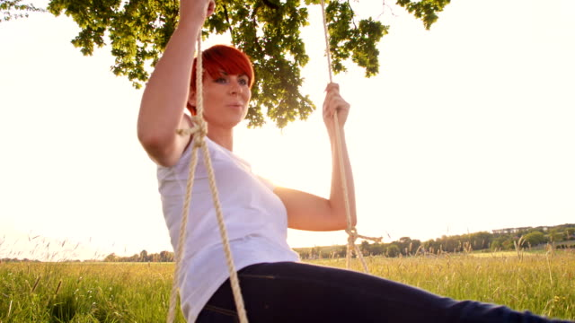 SLO MO Young woman swinging on a tree swing video