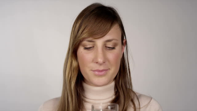 Young woman takes a pill and drinks water video