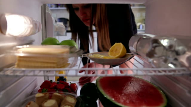 Young woman  takes cake from the fridge Young woman takes cake from the fridge fridge stock videos & royalty-free footage