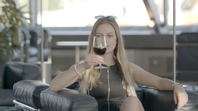 Young woman takes drink of wine in airport Female traveller navigates airport cross legged stock videos & royalty-free footage
