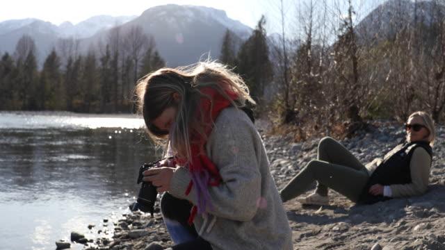 vídeos y material grabado en eventos de stock de mujer joven toma foto dslr en la orilla del río de montaña - memorial day weekend