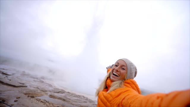 Young woman takes selfie at geyser in Iceland, slow motion video with geyser exploding on the background. people travel discover technology sharing concept -