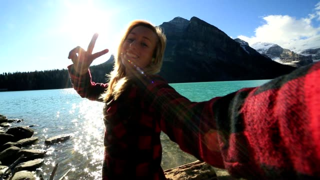 Young woman takes selfie at Lake Louise Young attractive woman taking selfie at Lake Louise. Beautiful mountain settings vanity stock videos & royalty-free footage