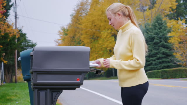 Young woman takes the mail from the mailbox. Countryside in USA
