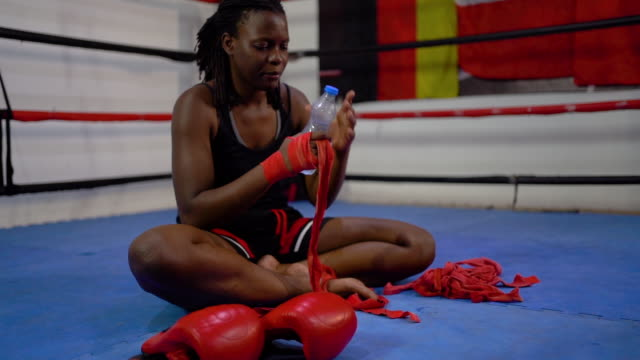 Young woman taking a break after a boxing training