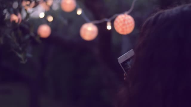 young woman taking a photo under lanterns video