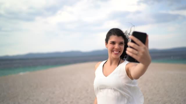 Young woman taking a selfie at the beach