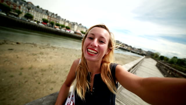 Young woman taking a selfie in Trouville harbour,Normandy-France Young woman taking a selfie in Trouville harbour,Normandy-France. Summertime on the coast. normandy stock videos & royalty-free footage