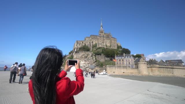 cneutrv1093 giovane donna prendendo una selfie foto a mont saint michel - manica video stock e b–roll