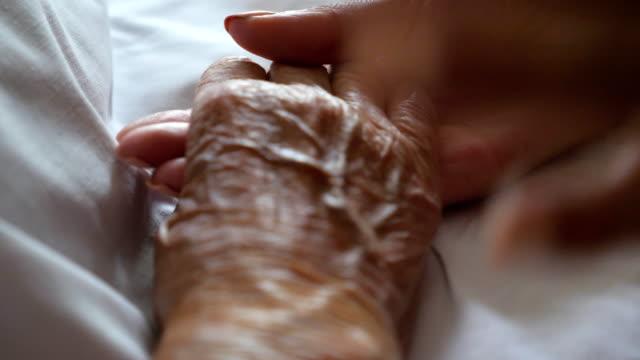 junge frau nimmt und sanft streicheln hand der kranken mutter, die unterstützung. tochter tröstet faltigen arm ihrer älteren mutter im krankenhaus liegend. konzept der pflege oder liebe. detailansicht zeitlupe - hände halten stock-videos und b-roll-filmmaterial