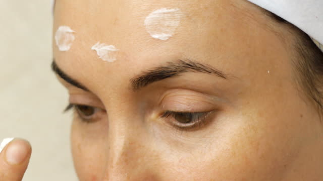 Young woman taking care of her face skin at home video