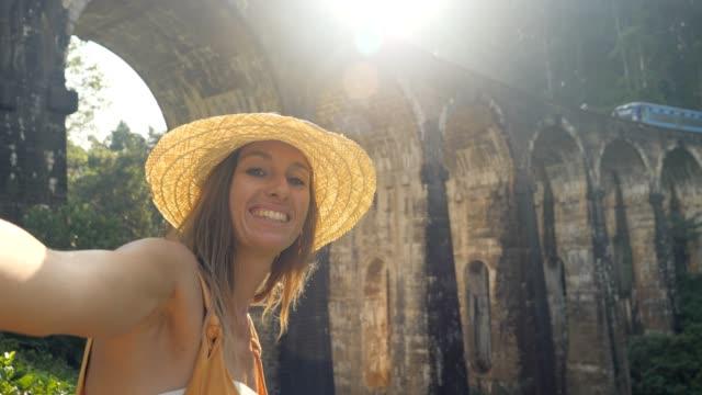 stockvideo's en b-roll-footage met jonge vrouw die koele selfievideo neemt die in sri lanka in beroemde sociale mediabestemmingen reist. - camelia white