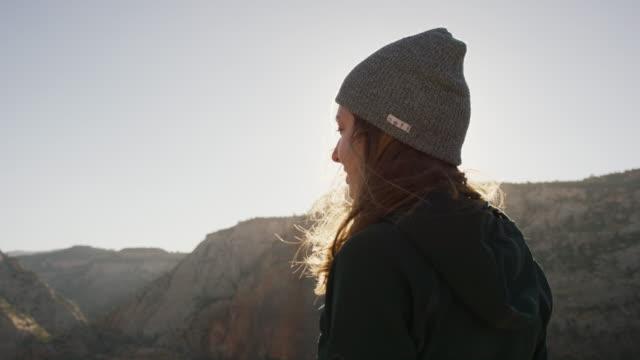 giovane donna che si prende la vista in cima a una scogliera - canyon video stock e b–roll