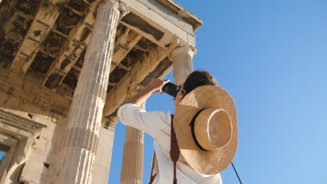 Young Woman taking pictures at Parthenon, Acropolis of Athens, Greece. Large hat, fashion white dress, sunglasses, smartphone. Young Woman taking pictures at Parthenon, Acropolis of Athens, Greece. Large hat, fashion white dress, sunglasses, smartphone. greek architecture stock videos & royalty-free footage