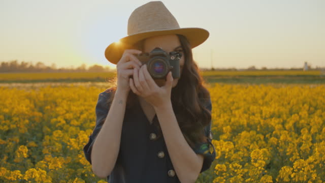 SLO MO MS Young woman taking pictures in field of rape
