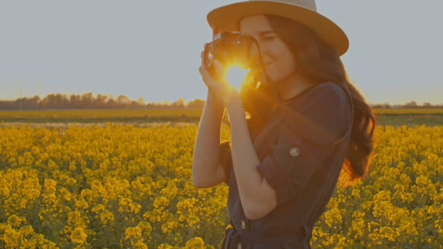 SLO MO MS PAN TU Young woman taking pictures in field of rape