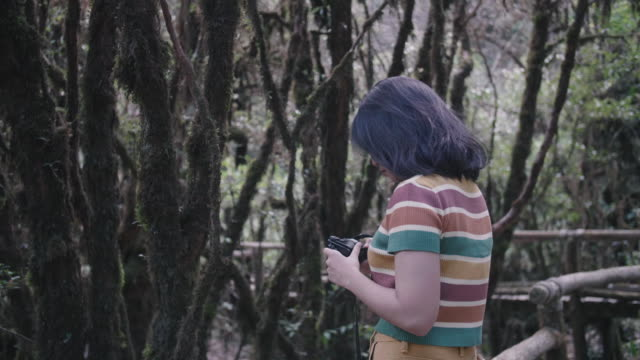 Young woman taking pictures in the Ang Ka Nature Trail.