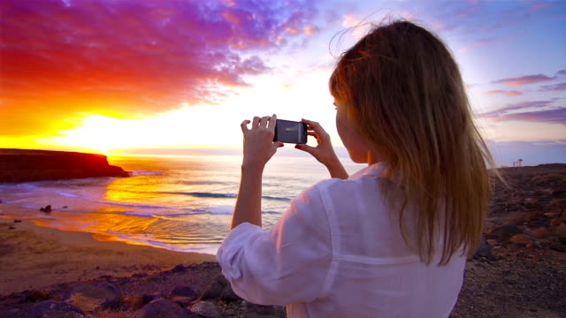 Young woman taking pictures of amazing sunset at beach video
