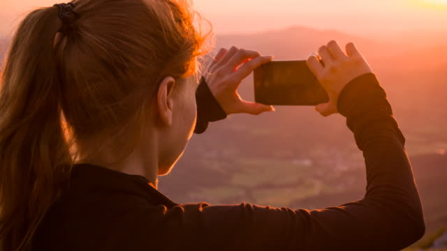 Young woman taking pictures of sunset with her smartphone video