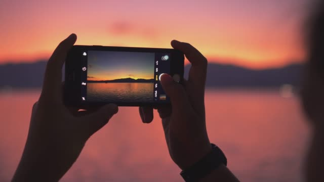 young woman taking pictures of the beautiful view with smartphone - foto video stock e b–roll