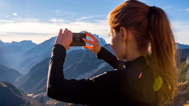 vídeos de stock e filmes b-roll de mulher capturar memórias com telefone - fotografar