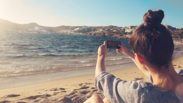 Young woman taking pictures with a smart phone. Young woman taking pictures with a smart phone. She is on the beach in a beautiful summer day. multimedia stock videos & royalty-free footage