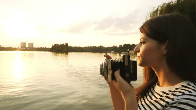 Young woman taking pictures with a vintage camera. video