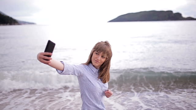 Young woman taking selfie at the beach