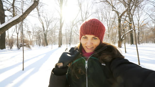 Young woman taking selfie in the winter park. video