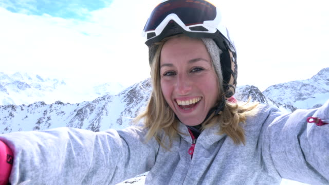 Young woman taking selfie on ski slopes video