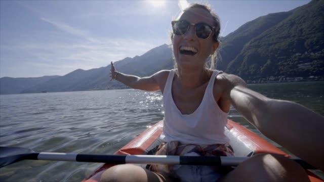 junge frau unter selfie porträt in rote kanu am berg see-eine weibliche genießen sommerferien spaß an outdoor-aktivitäten - zeitlupe - kanu stock-videos und b-roll-filmmaterial